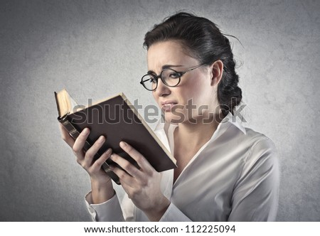 Girl with glasses reading a book - stock photo