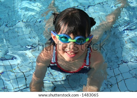 girl with goggle in the pool on sunny day