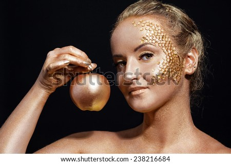 girl with golden bodyart posing with golden apple in her hands on black background - stock photo