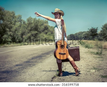 Girl with guitar on the road - stock photo