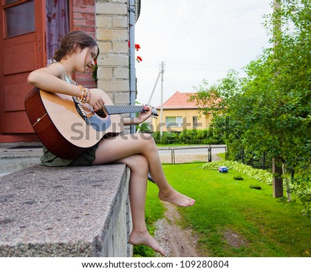 Girl with guitar outdoors - stock photo