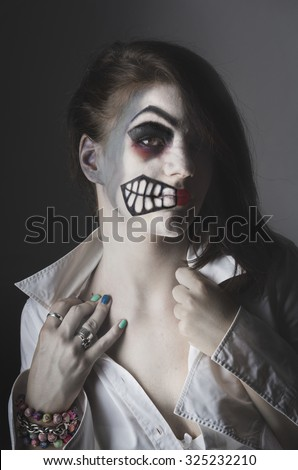 Girl with halloween mask on her face - stock photo