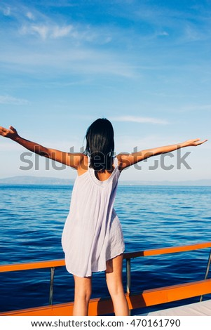 girl with hands up at the sea