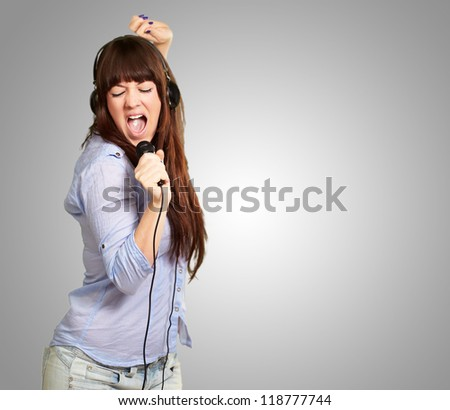 Girl With Headphone Singing On Mike On Grey Background - stock photo