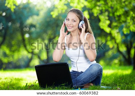 Girl with headphones and a laptop in the park - stock photo
