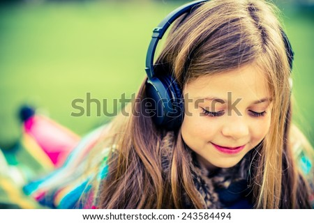 Girl with Headphones Listen Music While Relaxing in the Park. - stock photo