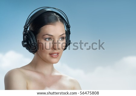 girl with headphones on the sky background - stock photo