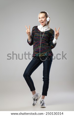 Girl With Headphones Singing and Dancing hands with V- sign. On grey Background. Full length portrait. - stock photo