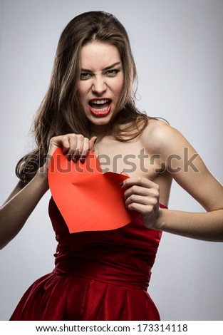 Girl with heart on gray background - stock photo