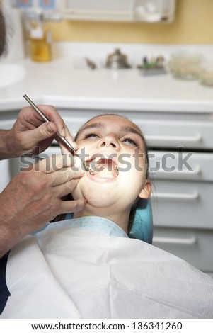 Girl with heavy toothache having her teeth checked by doctor