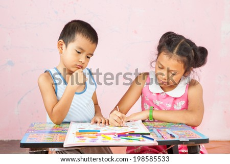 girl with her brother doing school home-work.