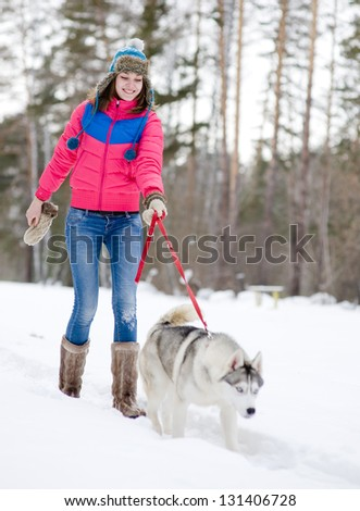 Girl with her cute dog in the winter forest - stock photo