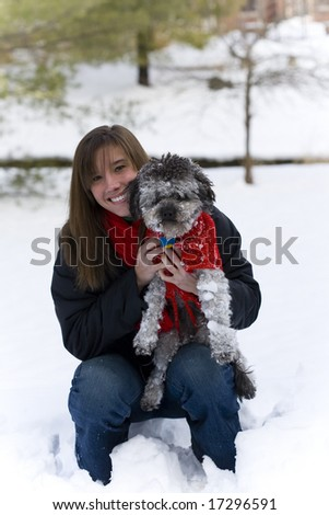 girl with her dog in the snow