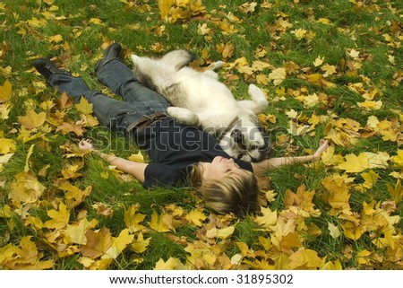 girl with her dog lying on the grass - stock photo