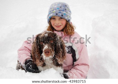 girl with her dog out in the snow