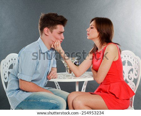 Girl with her drunk and sad boyfriend at table, in studio isolated on gray - stock photo
