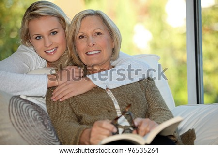 Girl with her grandmother reading a book - stock photo