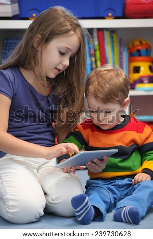 Girl with her little brother fun using a digital tablet computer