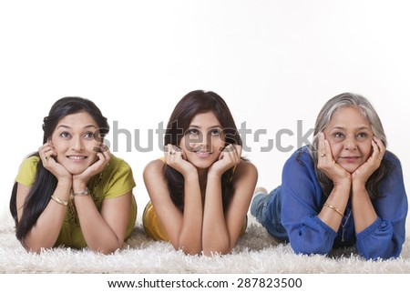 Girl with her mother and grandmother lying on carpet - stock photo