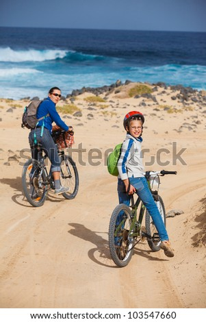 Girl with her mother having a weekend excursion on their bikes on a summer day in beautiful landscape. Vertical view - stock photo