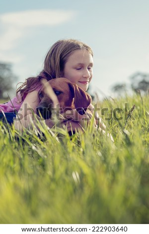 girl with her puppy in the grass, hugging - stock photo