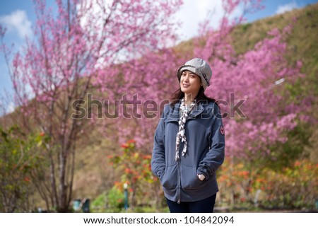 Girl with Himalayan Cherry (Prunus cerasoides) blooming at  Chiang Rai, Thailand.