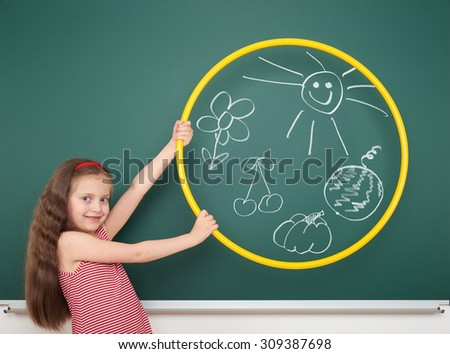 girl with hoop draw sun and flowers on board - stock photo