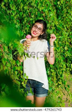 Girl with ice cream stands near a tree in the summer