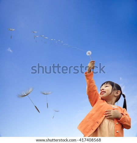 girl with is holding dandelion in hand while standing on with nice blue sky