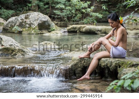 Girl with jar sitting by the creek. Woman sitting at a brook in the woods. Native woman relaxes with glass jug in tropical nature.