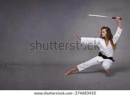 girl with katana ready to attack, dark background - stock photo
