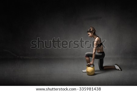 girl with kettlebell on hand, dark background - stock photo