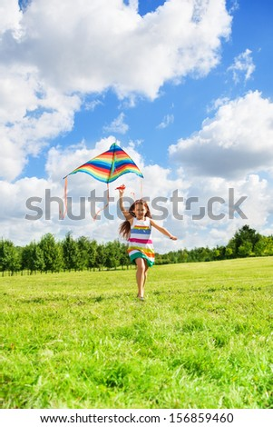 Girl with kids running in the field on sunny summer day - stock photo