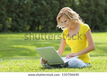 Girl with laptop. Blonde beautiful young woman with notebook sitting on the grass. Outdoor. Sunny day. Back to school - stock photo