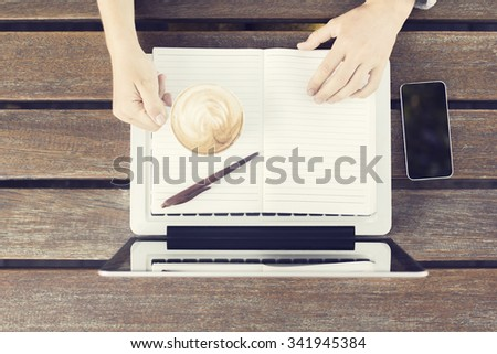 Girl with laptop, coffee mug, blank diary and cell phone on wooden table - stock photo