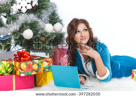 Girl with laptop lying under the Christmas tree