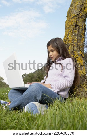 Girl with laptop sitting against tree - stock photo