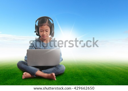 Girl with laptop sitting on green grass blue sky
