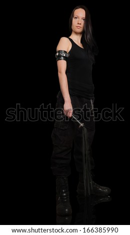Girl with lash in cargo pants with lash on black background - stock photo