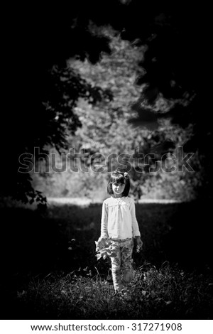 girl with leaves in hand in the woods