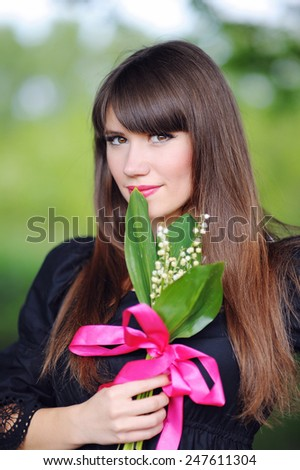 girl with lilies of the valley in the spring in the park. - stock photo
