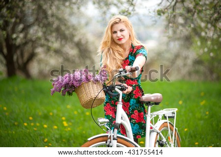 Girl with long blond hair wearing flowered dress looking at the camera keeps vintage white bicycle with flowers basket, against the blurred background of trees, greenery in spring garden. Front view