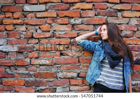 girl with long hair, dressed in a denim jacket and a scarf standing near a wall made of red bricks and waits