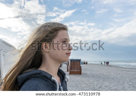 Girl with long hair is on the Baltic beach and looks at the sea / on the Baltic beach / girl