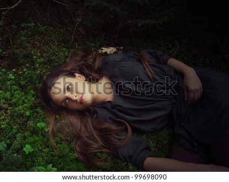 girl with long hair lying in the grass in the forest - stock photo