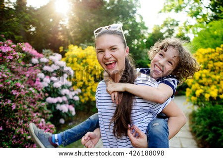 Girl with long hair on the shoulders bears the 8-9 year-old boy. Both laugh. Behind them, a beautiful flowering shrub