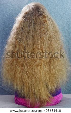 Girl with Long Wavy Blond Hair, sitting on a coach; Rear View - stock photo