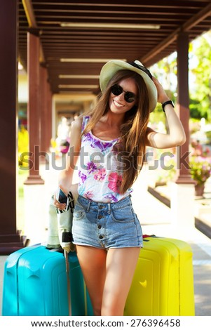 Girl with luggage at airport.tanned girl with large suitcases and watch, waiting for departure,holding straw hat,cool sunglasses,map,bright summer clothes colors,denim shorts,fashion,cool accessories  - stock photo