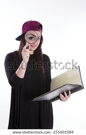 Girl with magnifier and book on white background - stock photo