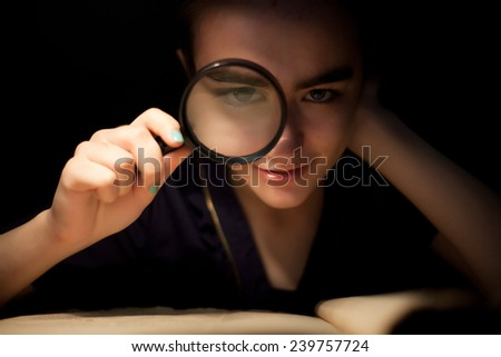 Girl with magnifir glass front eye looking - stock photo